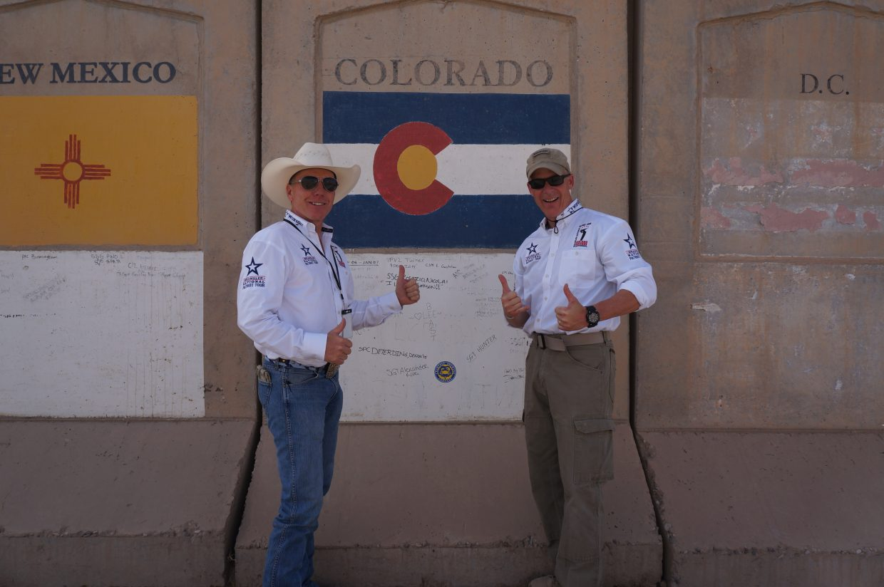 From left, Jeff Chadwick and Rob Powers pose in front of a Colorado state flag in Iraq on Memorial Day. The duo is traveling on the Armed Forces Entertainment Wrangler National Patriot Memorial Day Tour, featuring Champion cowboys and cowgirls, along with Nashville artists. Submitted by Rob Powers.