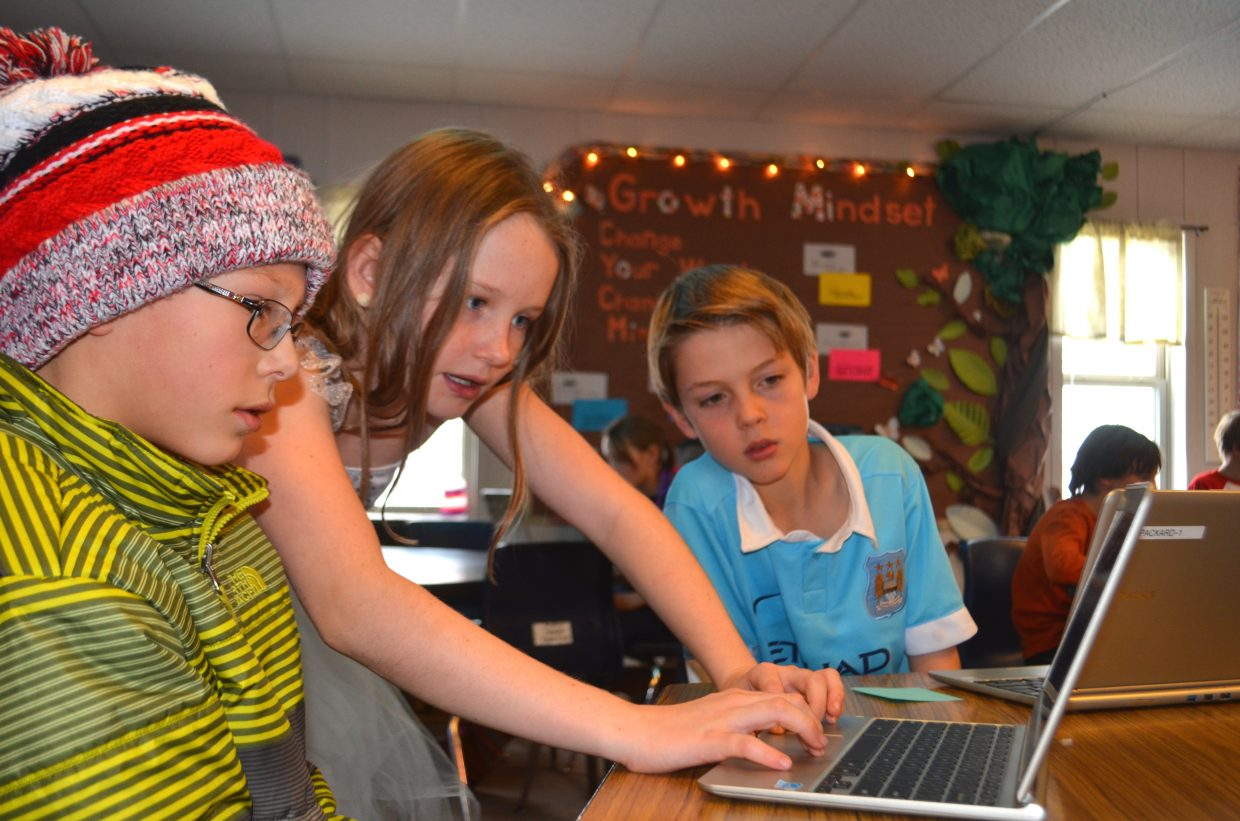 Fifth-grader Lucy Travis shows her classmates Charlie Welch and Tomas Niedermeier a few techniques on TinkerCad.
