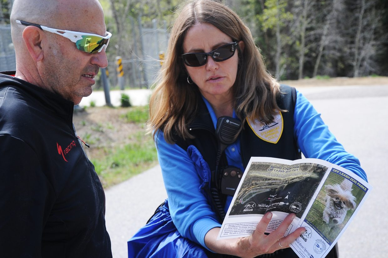 Animal Control Officer Jennifer Good tells dog walker Larry Bookman where the local off-leash dog parks are on Friday. Some community members are calling on the city to expand the number of dog parks.
