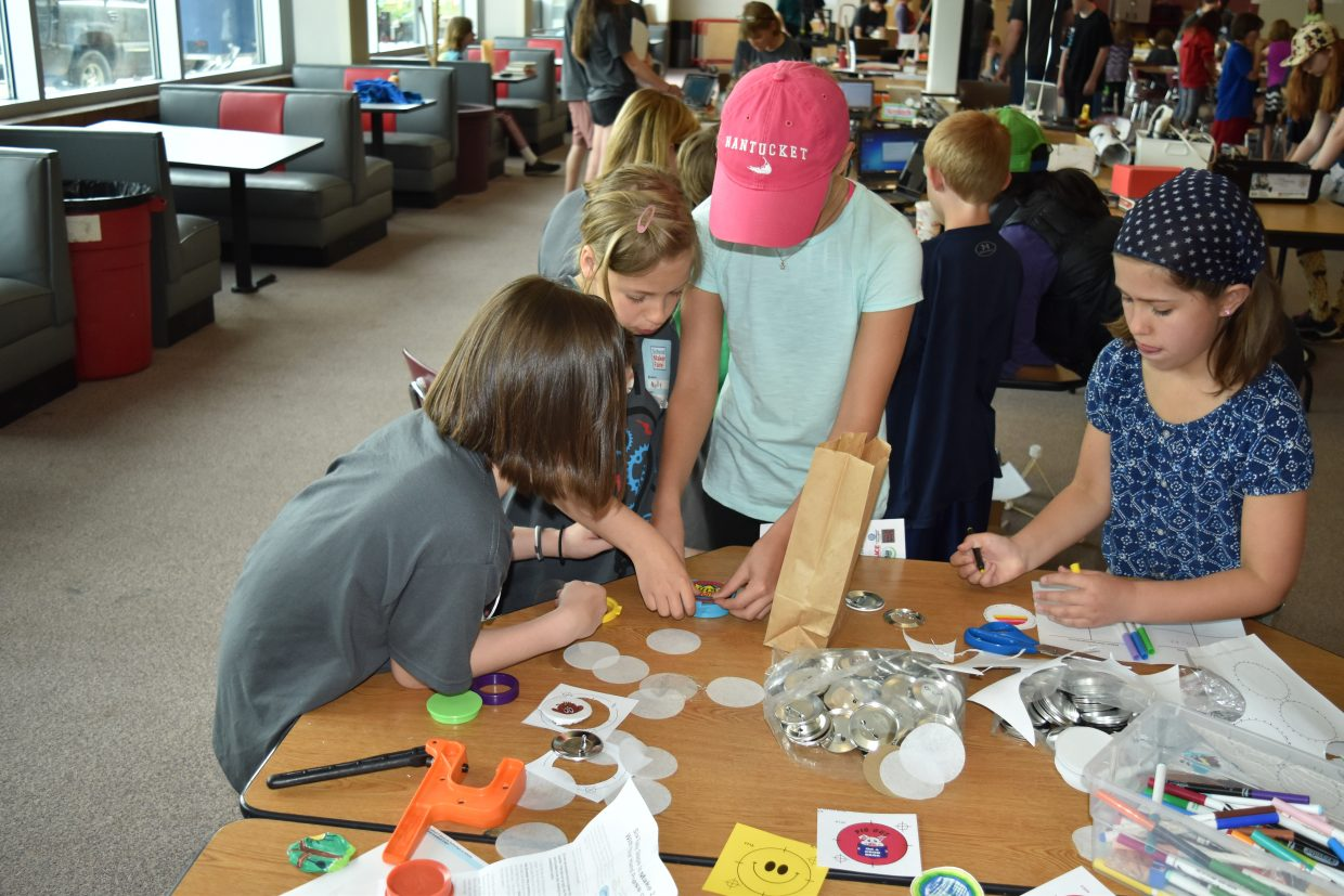 In this photo: kids at the Maker Faire take part in button making