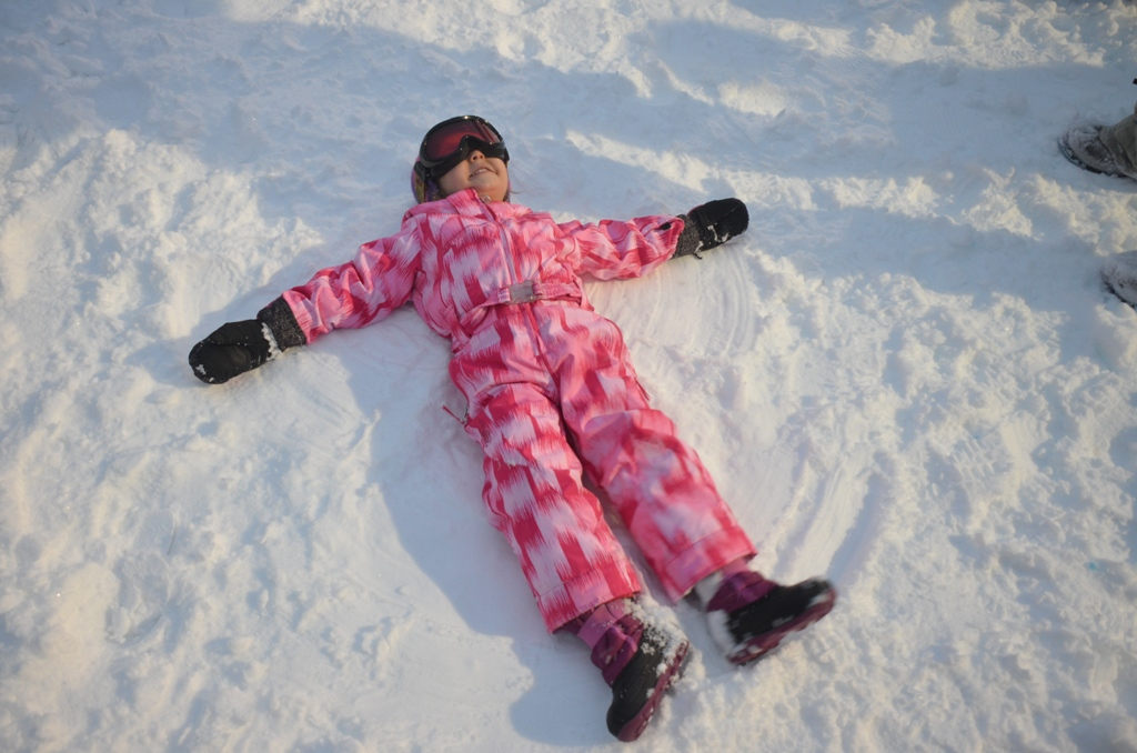 Abigail Malkowski makes snow angels in the snow during Sunday night's Community Holiday Party at Howelsen Hill, hosted by the Rotary Club of Steamboat Springs.