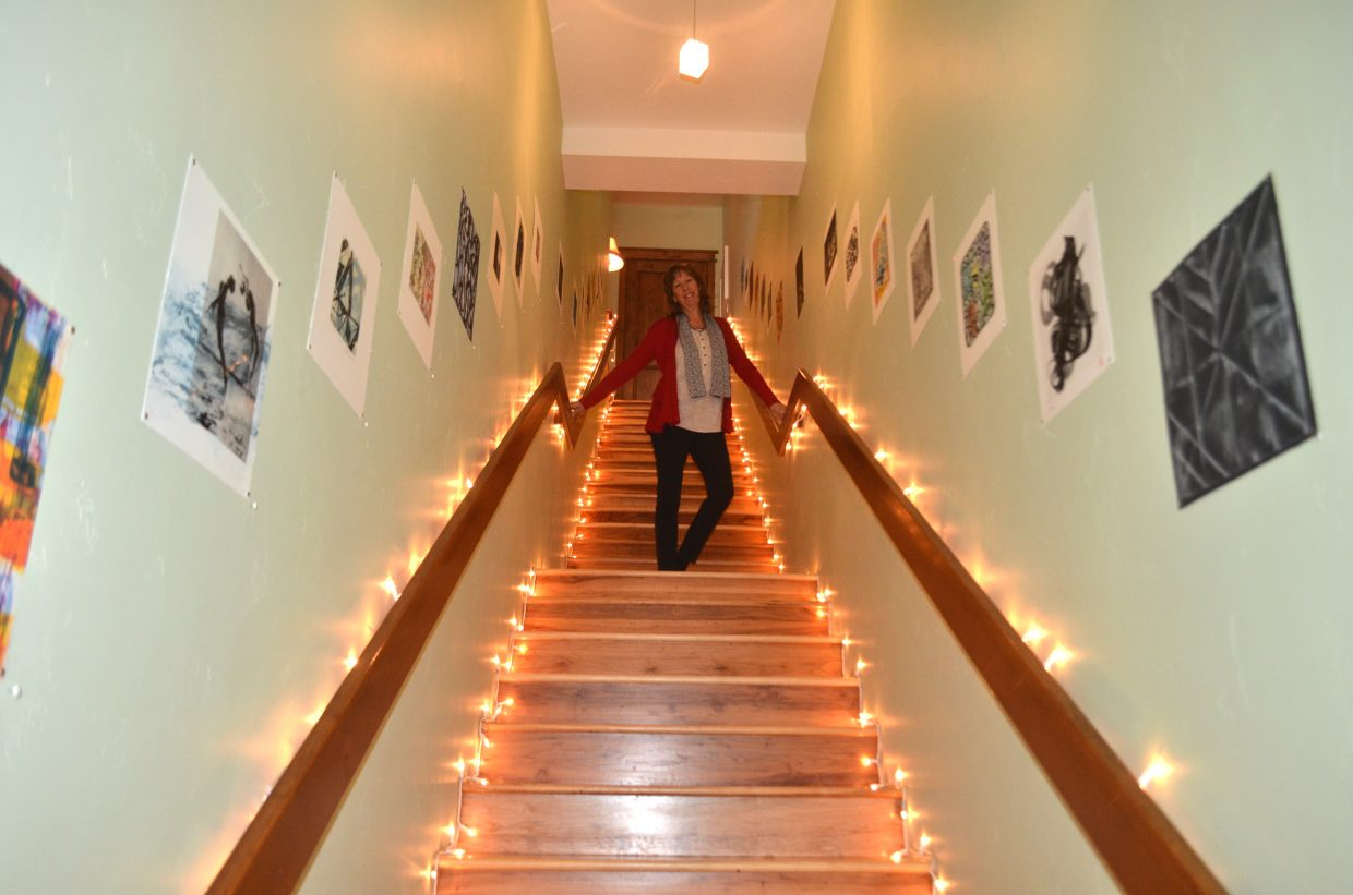 "Master Printer, founder and owner of Oehme Graphics stands in the ""Stairway to Heaven"" stairwell that holds significance to her dream of opening a printmaking studio and showcases a variety of prints from over 45 renowned artists who have visited the studio in the past five years."