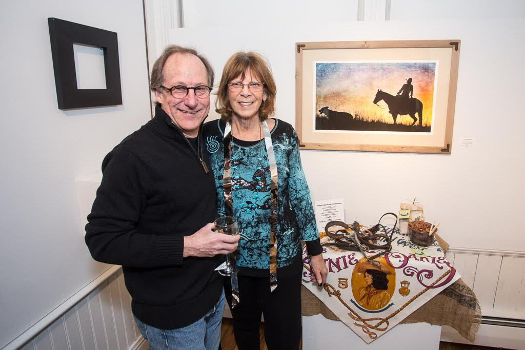 "Karen and Joel Schulman stand near her photograph ""Cowgirl's Sunset Ride"" printed by Joel. Local rancher Susan Shoemaker is featured in the piece."