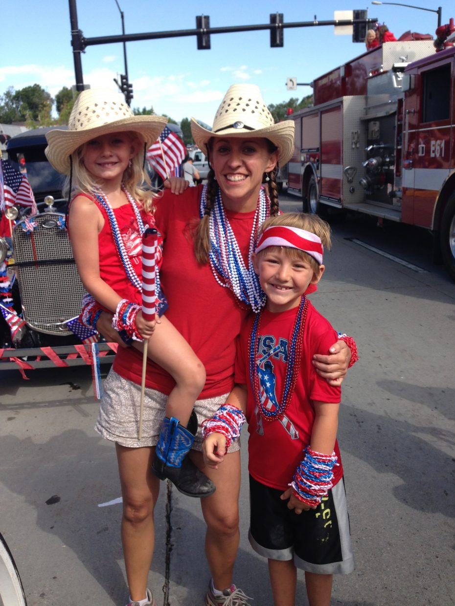 Becca Moore and kids, walking with presenting sponsor Yampa Valley Bank, ready to give out swag in the 2014 4th of July Parade