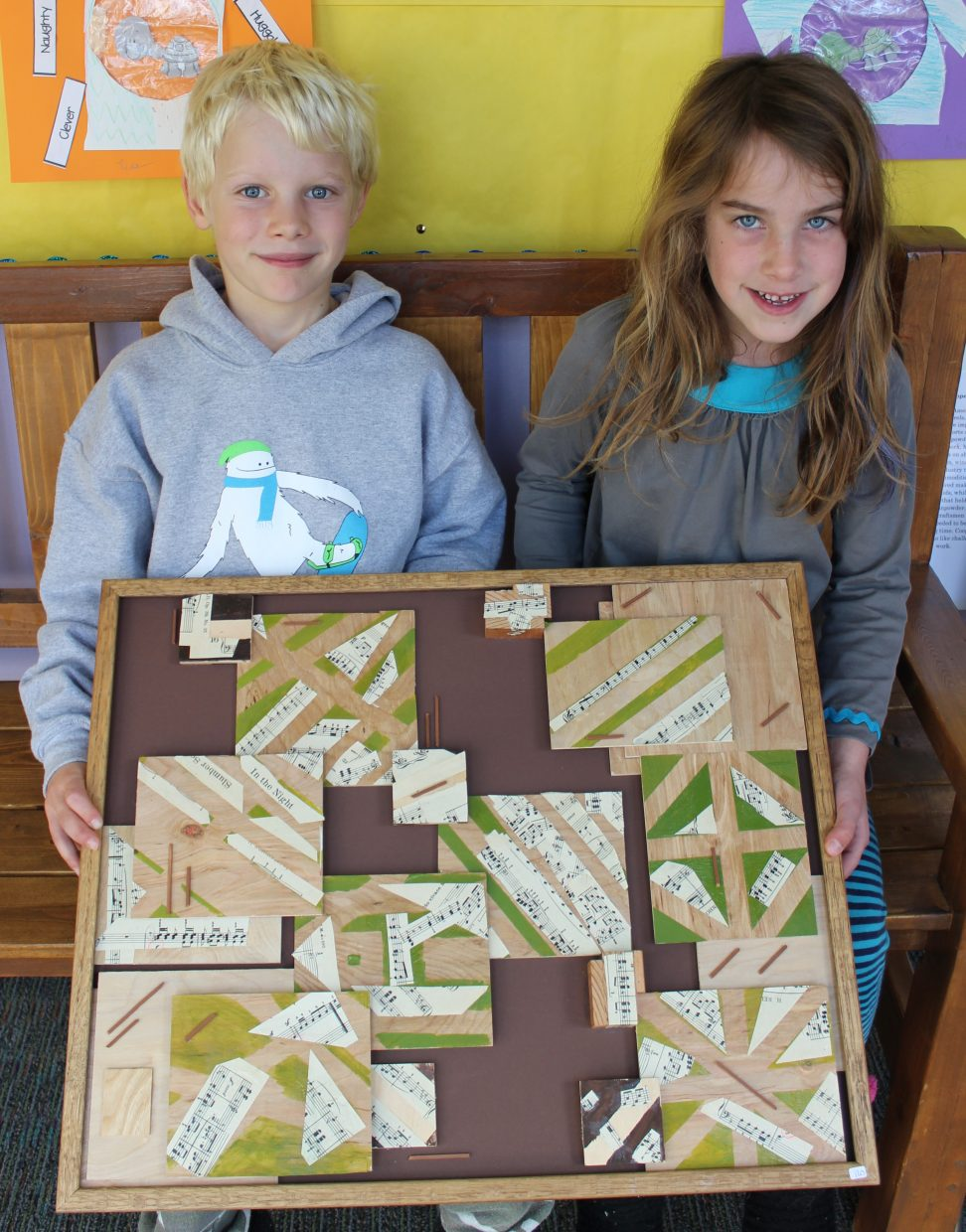 """Emerald Mountain School second graders Weston Worley and Caley Goforth hold the second grade art project """"Music to Our Ears,"""" which will be auctioned off Saturday as part of the school's annual fundraiser to provide scholarships to students."""