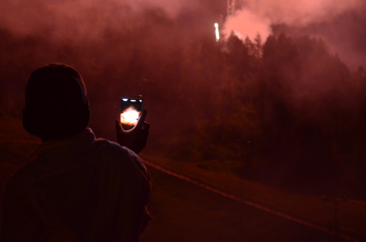 A man shoots video on his cell phone of red fireworks bursting just north of the Howelsen Hill ski jumps Friday night for the Fourth of July show.