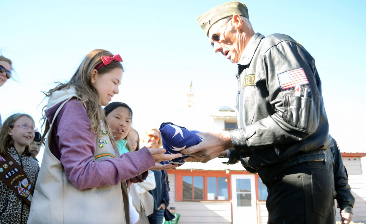 Steamboat Springs Girl Scout Sidney Barbier gets shown the proper way to present a flag by Army veteran Fred Sandelin. On Sunday at the Stanko Ranch, Steamboat Springs Girl Scouts and the Girl Scout Cadette Troop 3725 worked with local veterans on the proper process of inspecting, judging and deeming worn flags as unservicable during a flag retirement ceremony.
