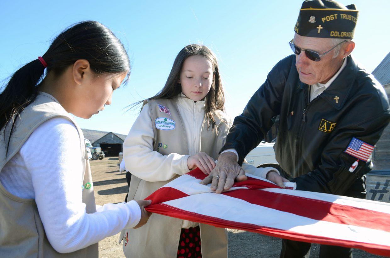 Steamboat Springs Girl Scouts Annie Hager, left, and Natasha Curzon work with Army veteran Fred Sandelin on the proper way to fold an American flag as it gets set to be retired.