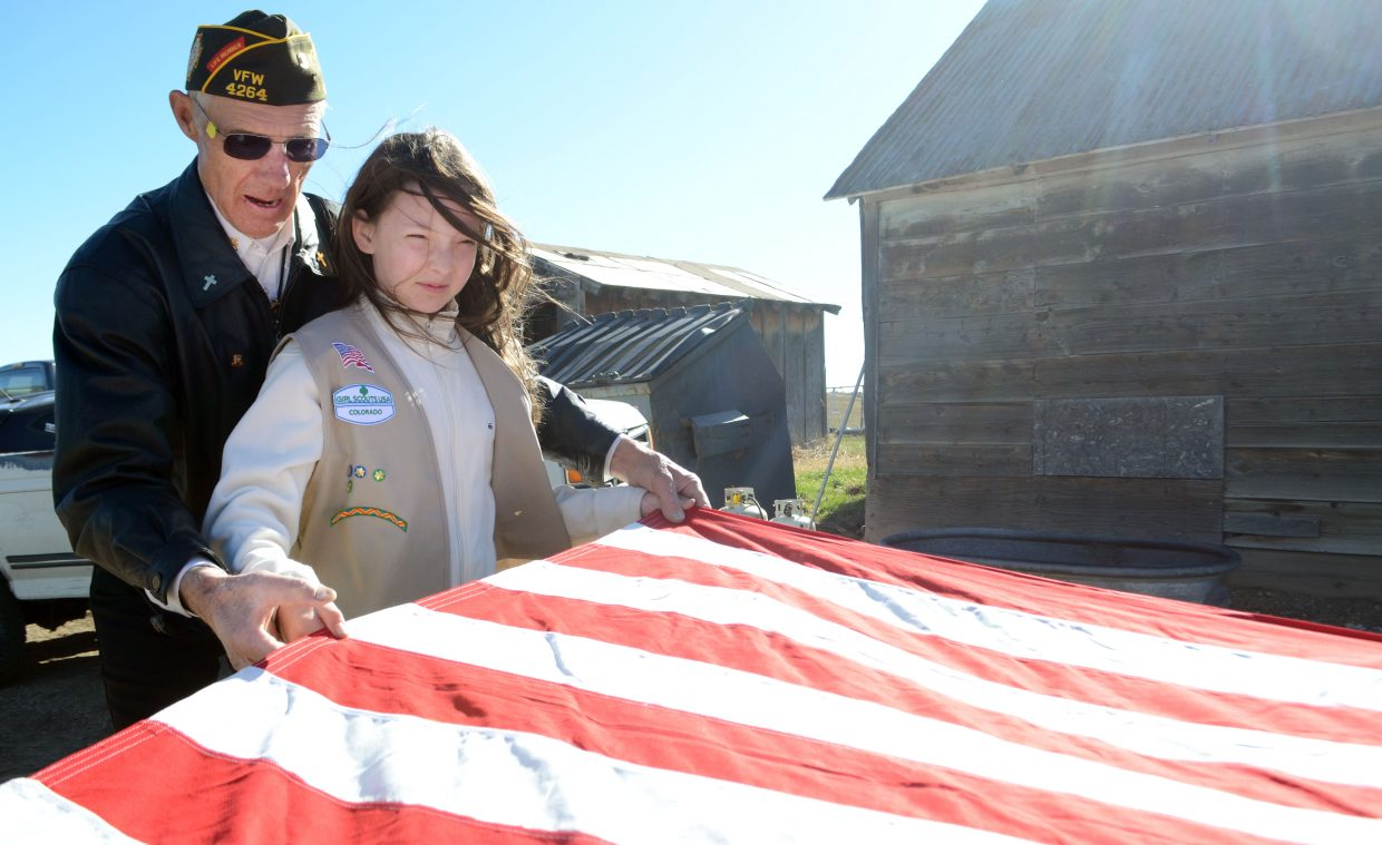 Girl Scout Natasha Curzon works with Fred Sandelin to fold up an American flag on Sunday.