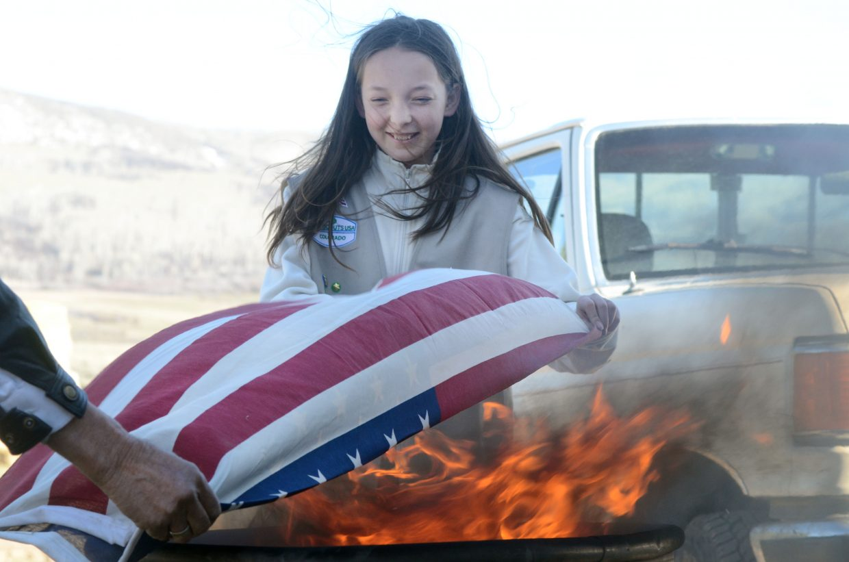 Girl Scout Natasha Curzon retires a worn American flag on Sunday.