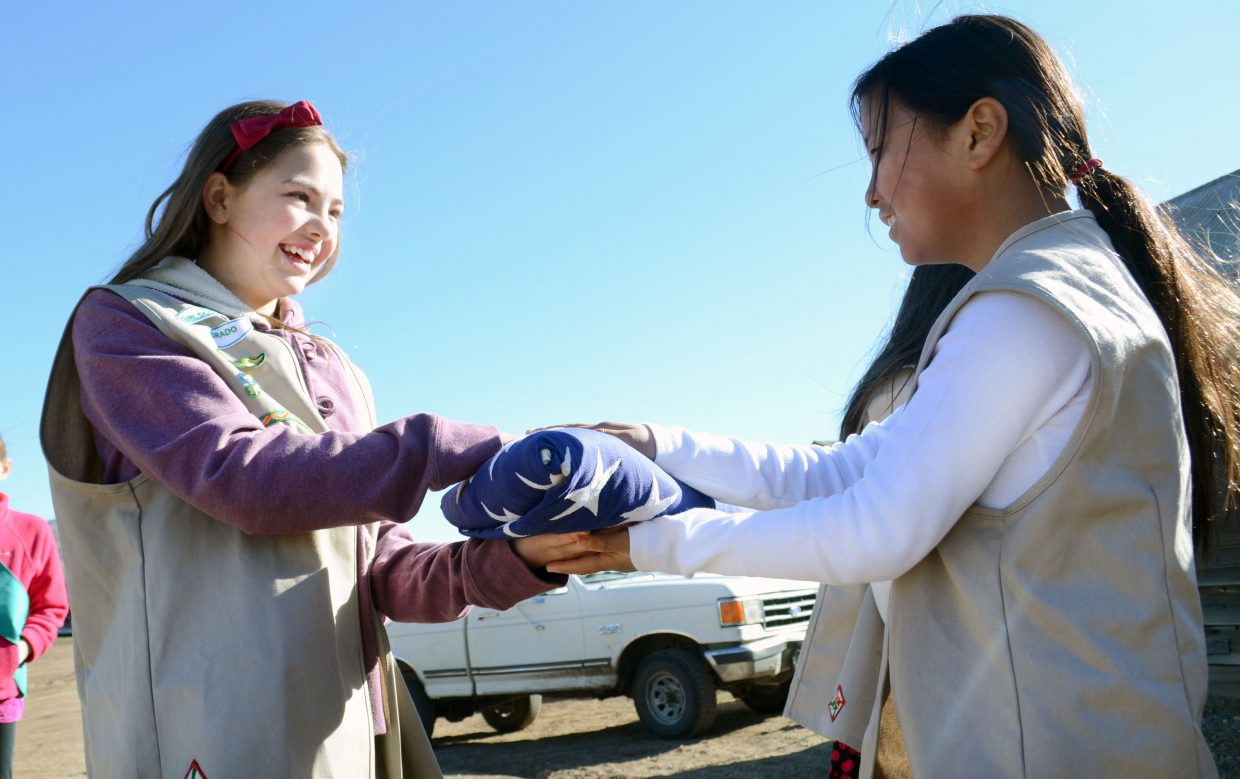 Girl Scouts Sidney Barbier, left, and Annie Hager practice properly presenting an American flag to one another on Sunday.