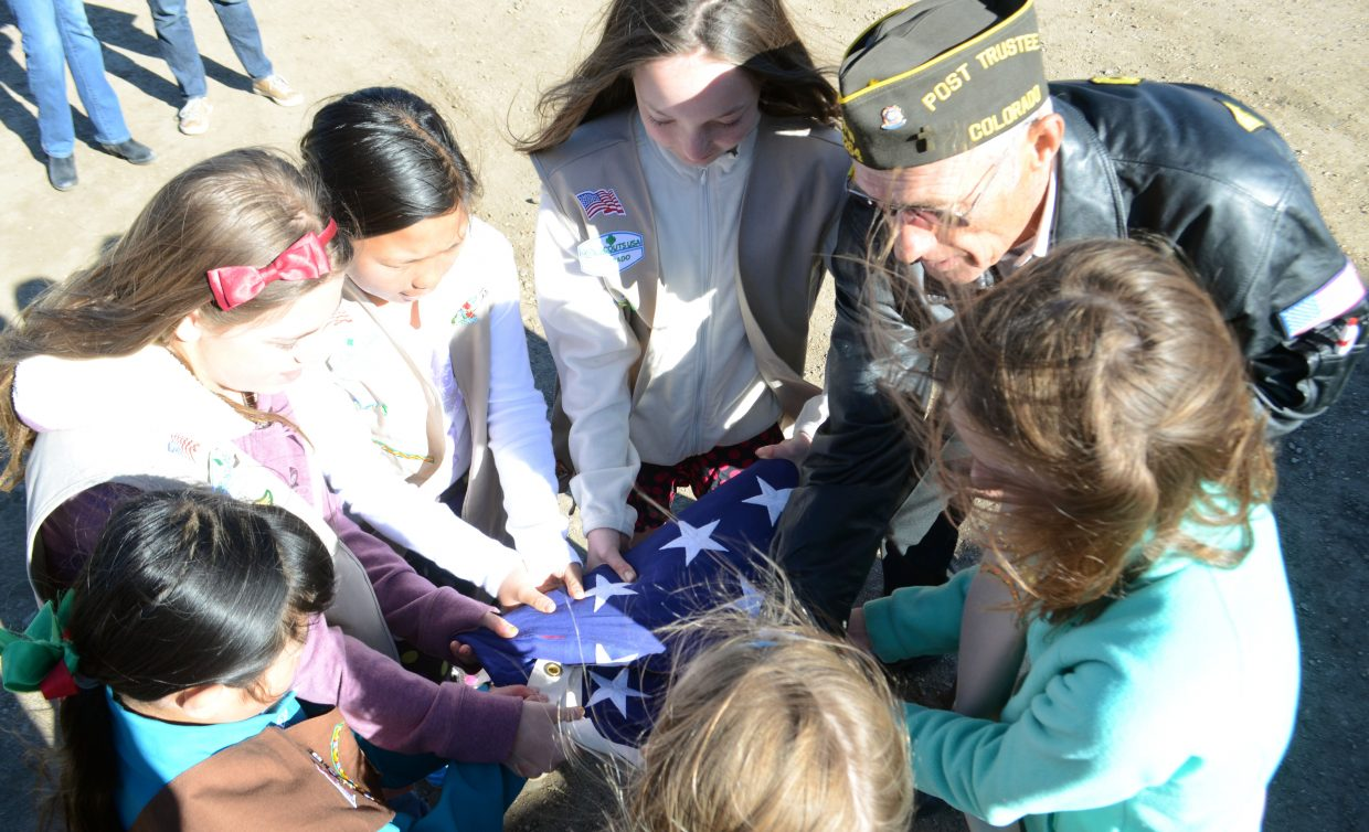 Veteran Fred Sandelin helps a group of Steamboat Springs Girl Scouts properly fold an American flag on Sunday.