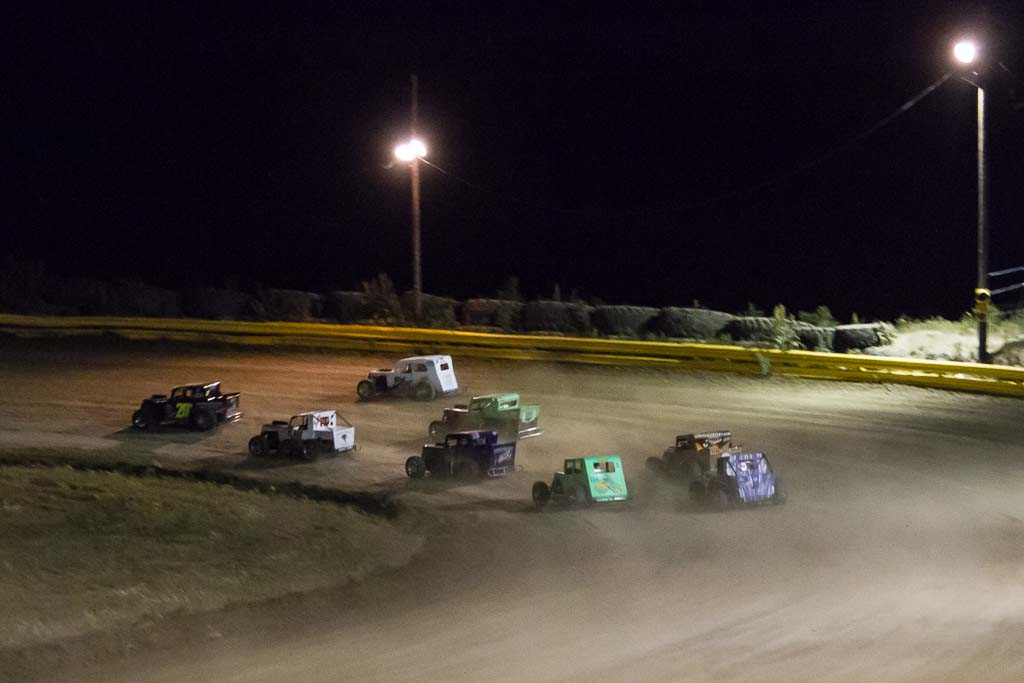 Action under the lights at Hayden Speedway Saturday night in the Dwarf class feature race. Dwarfs are scaled down replicas of vintage coupes, highly modified with powerful engines. Submitted by George Fargo.