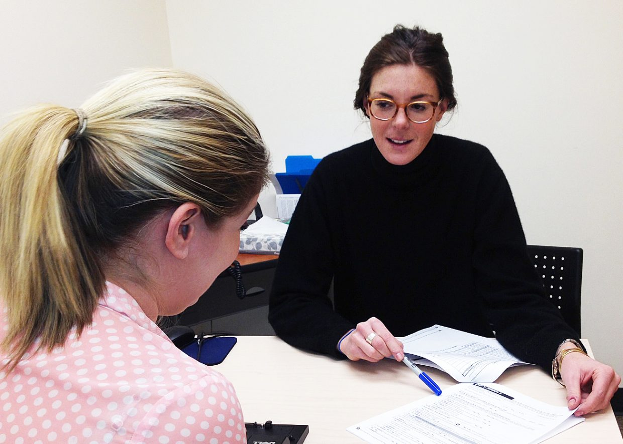 Erin Gleason, former community and small business health insurance coordinator for the Northwest Colorado Visiting Nurse Association, talks a resident through the process of signing up for insurance earlier this year. Open enrollment for health insurance runs from Nov. 1 through Jan. 31, 2016.
