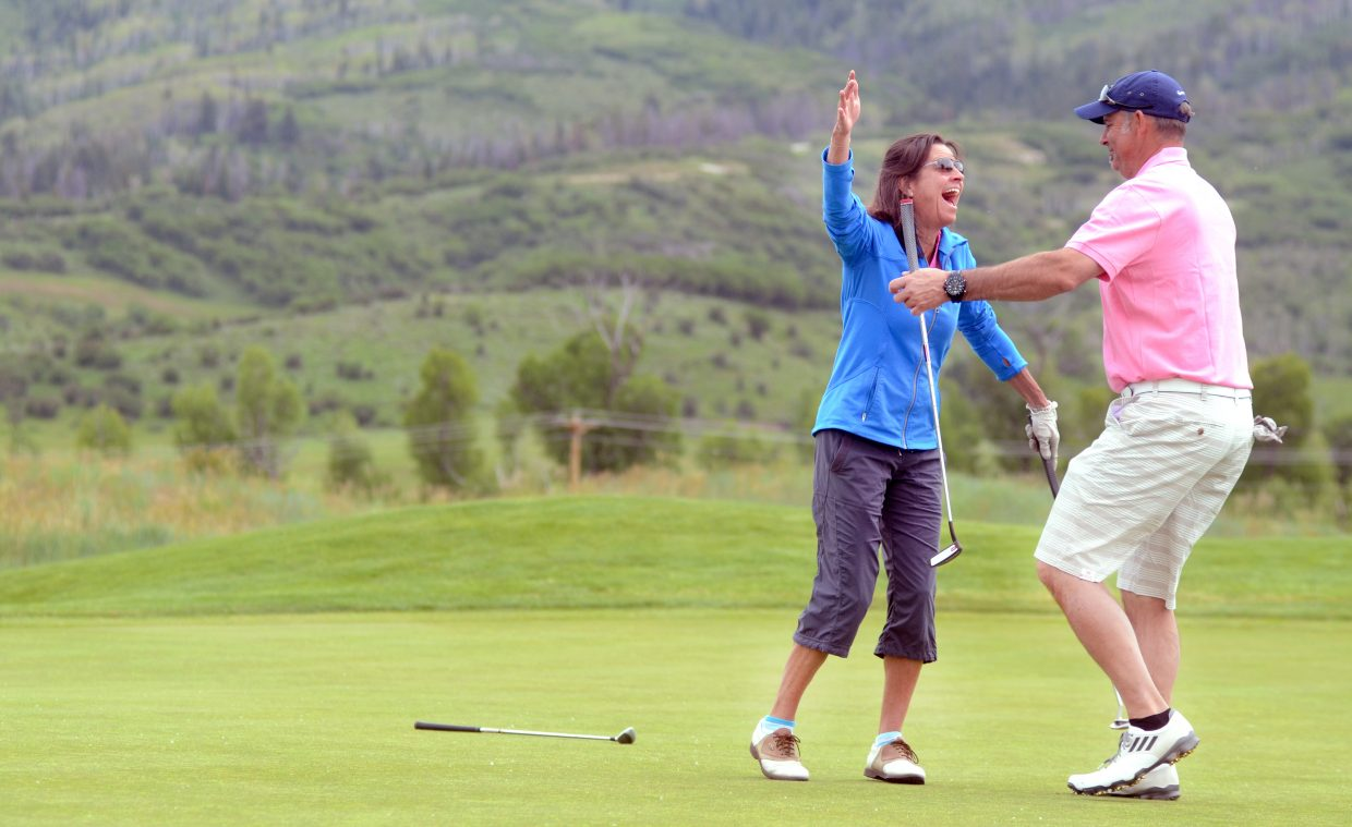 Patti Curry and Ernie Thiel celebrate Curry's lengthy putt on No. 6 at Haymaker Golf Course on Saturday afternoon during Day 2 of the Ski Town USA Golf Classic. Other Ski Town Classic golfers were at Rollingstone Ranch Golf Club finishing up the tournament.