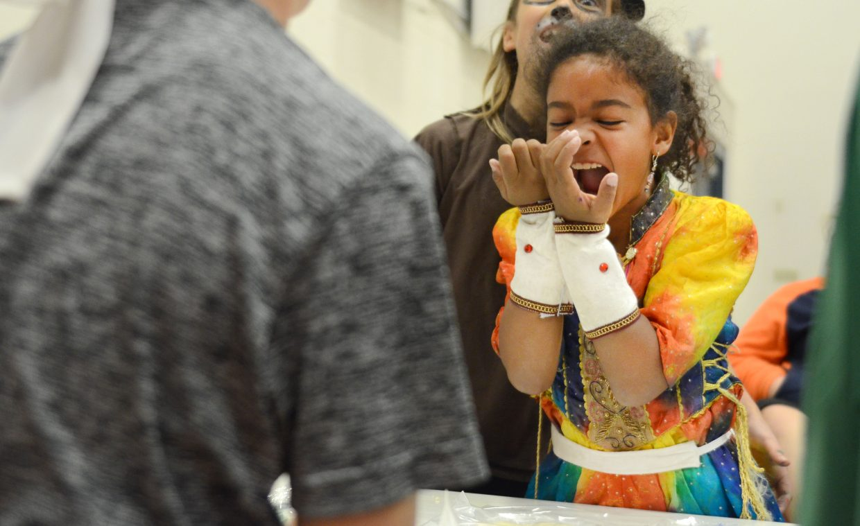 """Heritage Christian School third-grader Davina Grant gets a burst of excitement while flattening hand-made corn tortillas as school Friday. The school celebrated its annual fall festival just before the weekend, with this year's theme of """"Around the World."""" Students went through various stations dressed in cultural regalia and participated in different country-themed activities."""