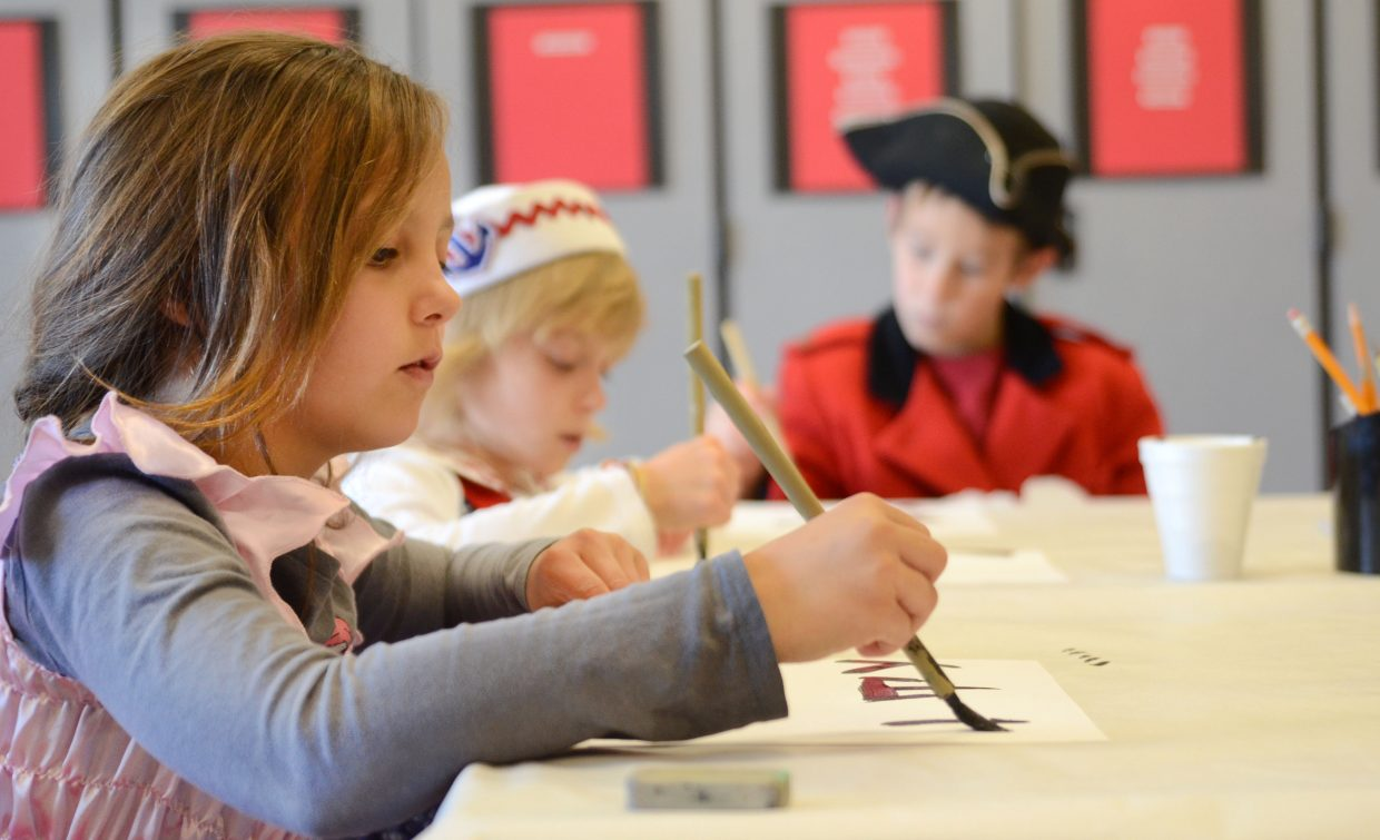 """Heritage Christian School second-grader Peyton Baker paints some Mandarin Chinese numbers and symbols Friday during the school's """"Around the World"""" themed fall festival."""