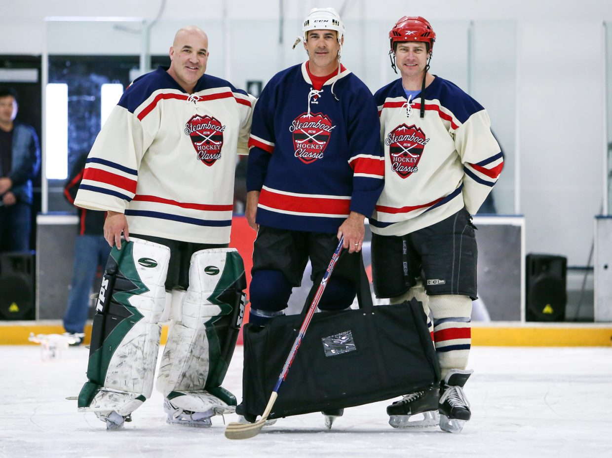 National Hockey League alumnus Keith Carney, center, representing the NHL Players' Association, presents a gift to Chris Campanelli, left, and Kerry Shea, of Steamboat Youth Hockey, during the third annual Steamboat Hockey Classic at Howelsen Ice Arena.