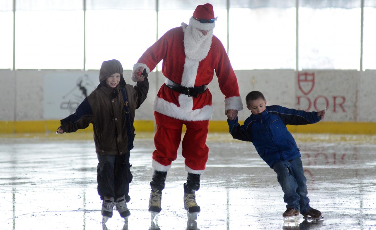 Curtis Canfield, 9, and Ryden Thomas skate with Santa Claus on Saturday afternoon at the ice rink in Oak Creek as part of the final day of the Holly Festival.