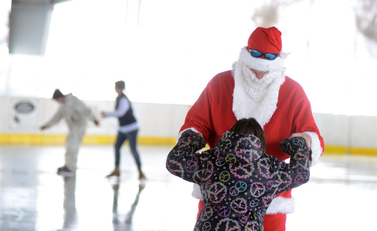 Santa Claus helps Oak Creek's Reina Thomas, 10, keep balanced on her skates Saturday afternoon during one of the Holly Festival events in town.