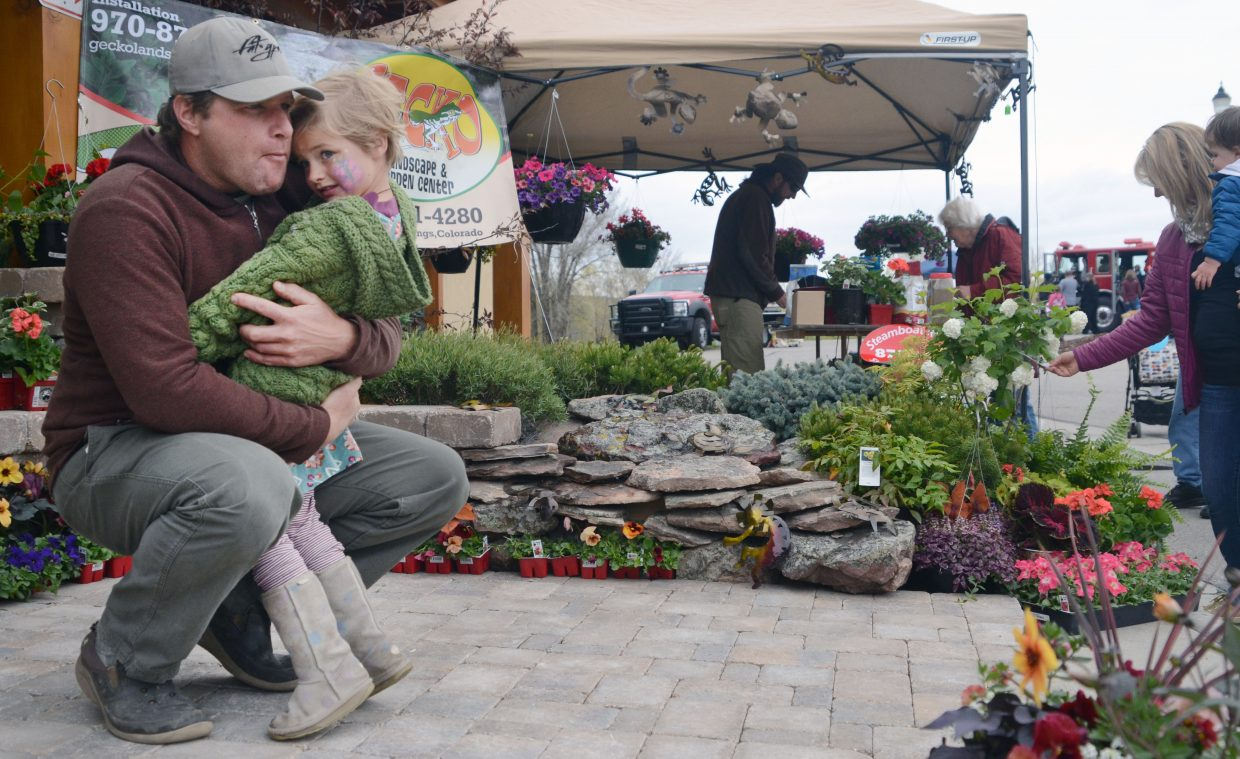 Mike Higgins hugs his daughter, Charlotte, at the Gecko Landscape & Garden Center's deck presentation outside the Steamboat Springs Community Center for the Home and Garden Expo.
