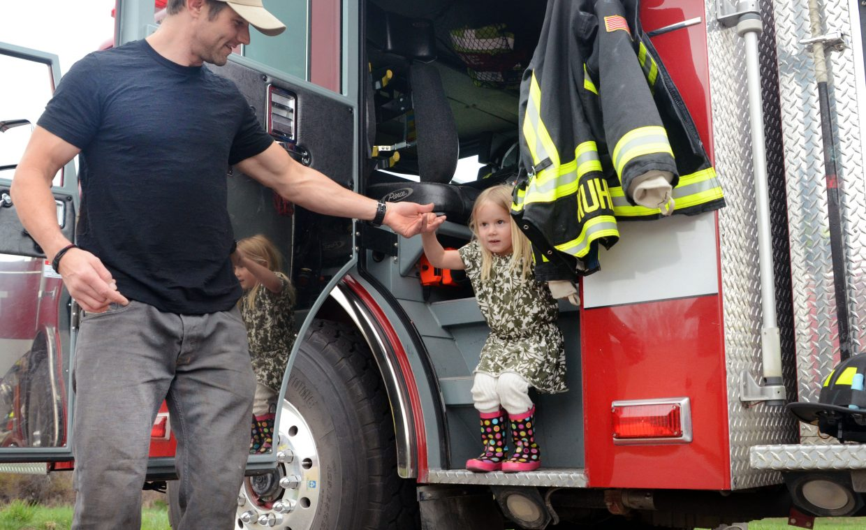 Lucas Johnson, left, helps his daughter, Saylor, out of a Steamboat Springs Fire Department engine at Saturday's Home and Garden Expo.