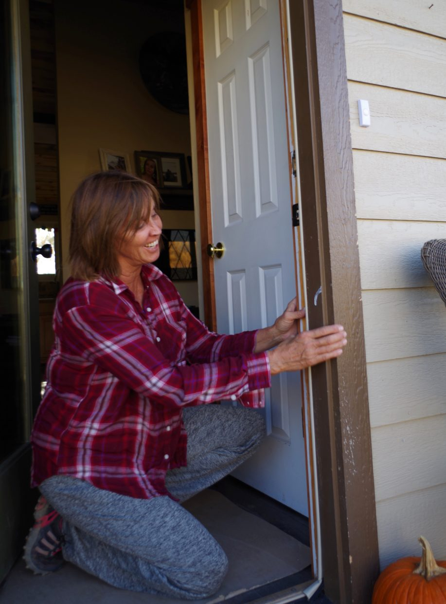 Homeowner Joanie King, who recently received a residential energy audit sponsored by Yampa Valley Sustainability Council, replaces worn weather stripping on her home's front door.