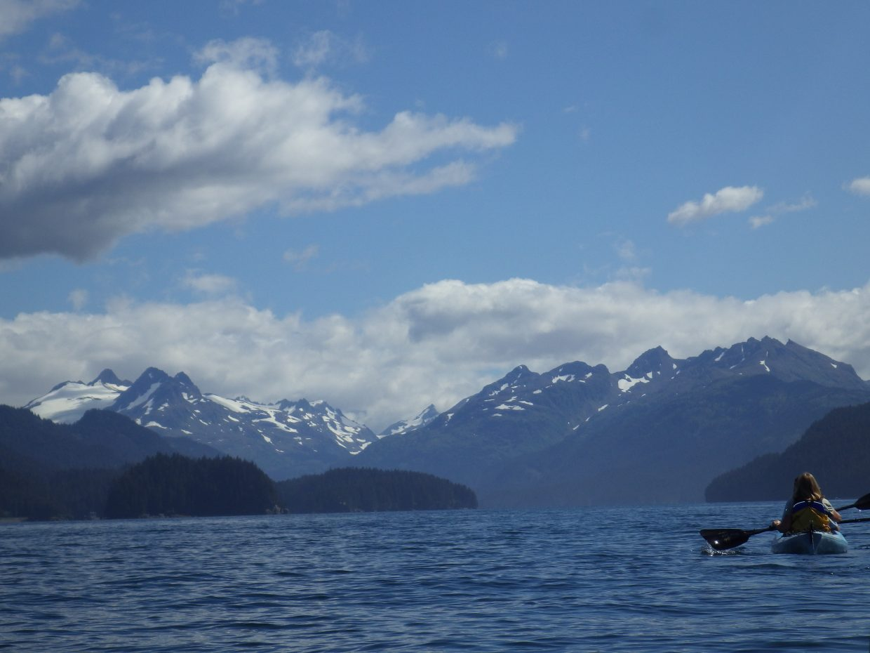 Paddling away from the cabin toward Tutka Bay and the jagged range of the Chugach mountains.