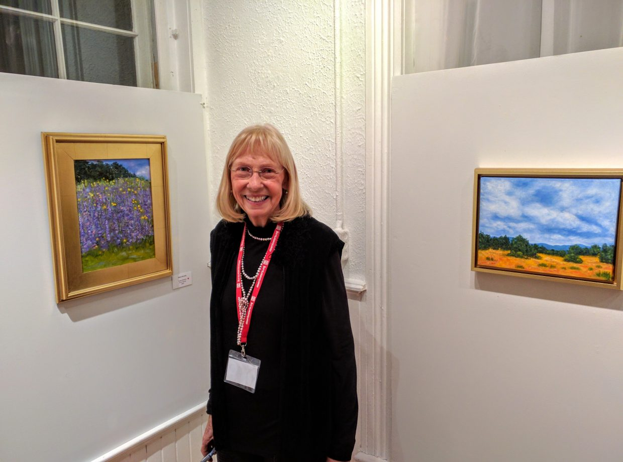 Steamboat Springs artist Elaine Dermody stands next to a few of her paintings, which are currently on display at the Depot Arts Center.