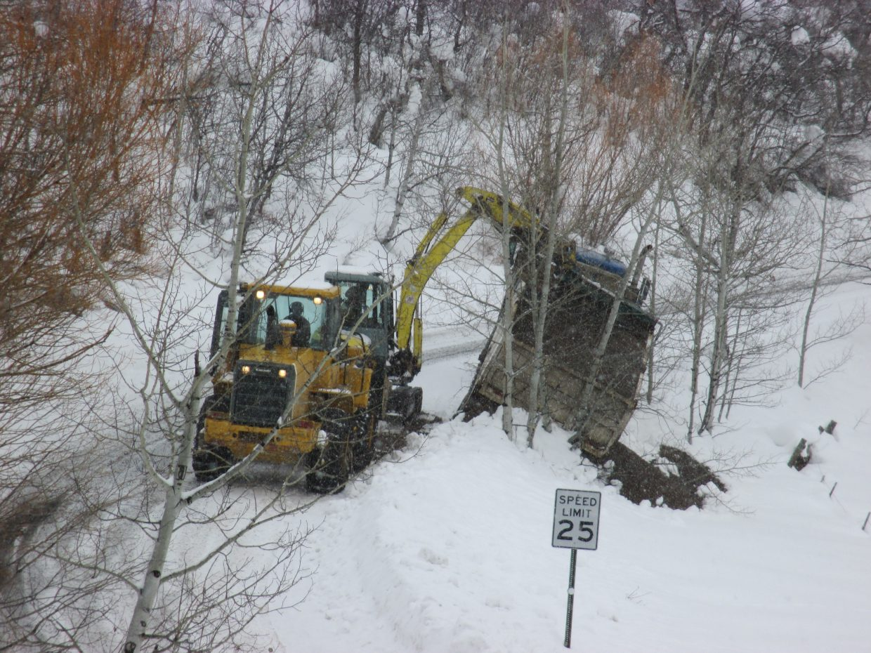"""""""Dump truck getting unloaded so it can be extracted from the hill it slid down on Thursday."""" Submitted by Shelly McGhan."""