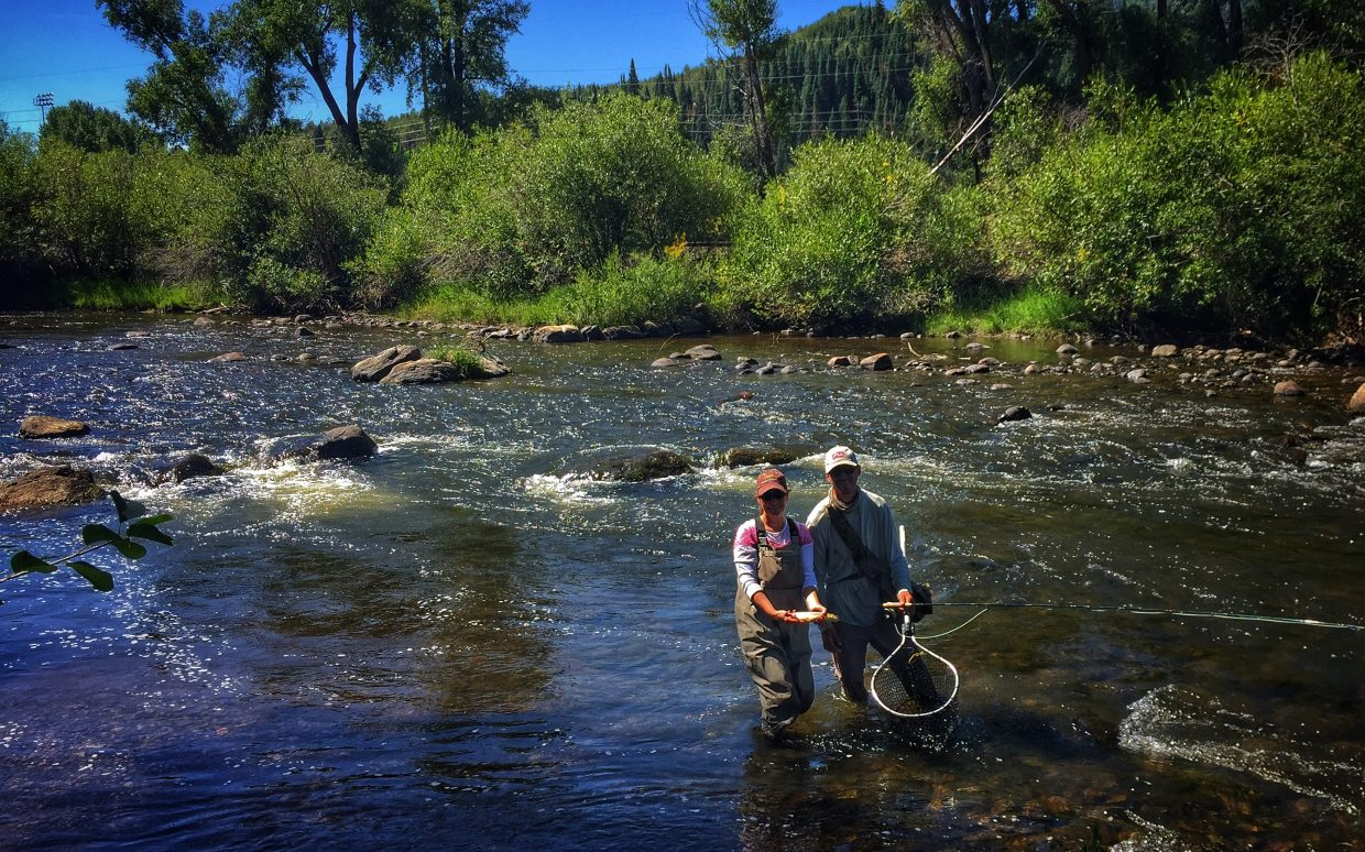 Andy from Steamboat Fly Fisher with a never-ever fly fishing client on the Yampa River. I saw her catch 3 nice Browns Saturday morning behind E3 Chophouse.