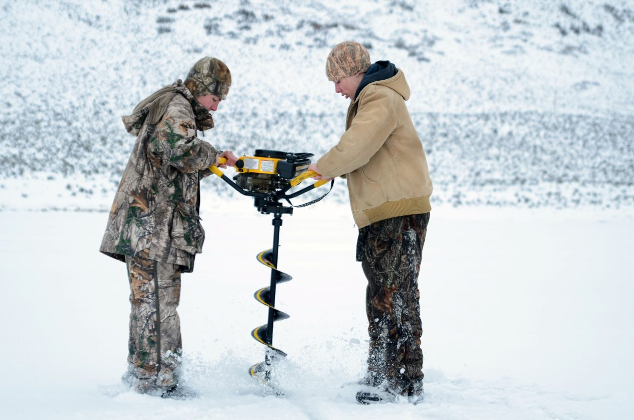 Dawson Baucke and Joey Spencer drill an ice fishing hole Sunday at Stagecoach Reservoir during the Steamboat Great Outdoors Ice Fishing Tournament.