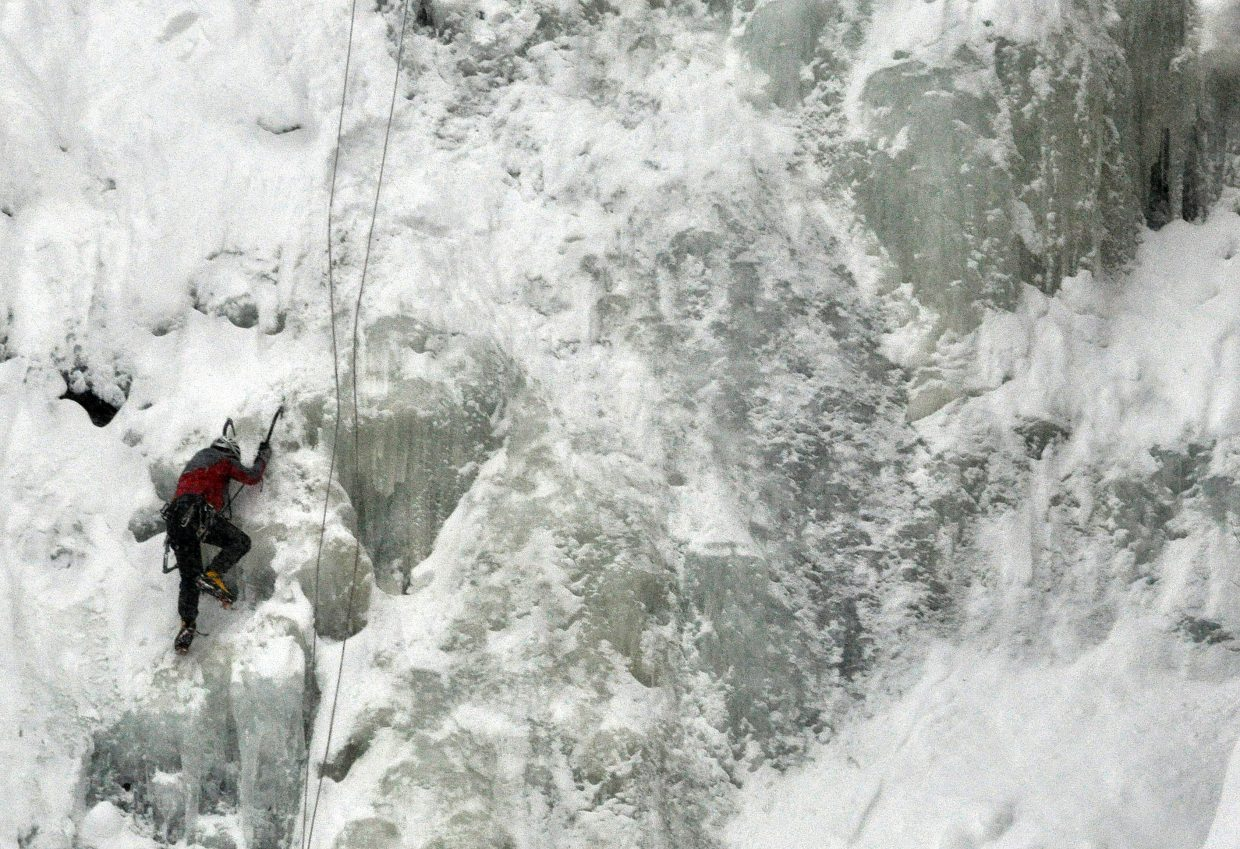 Dan Smilkstein climbs up a frozen Fish Creek Falls on Sunday afternoon. Frigid temperatures and snow showers didn't stop the climber from making a quick ascent.