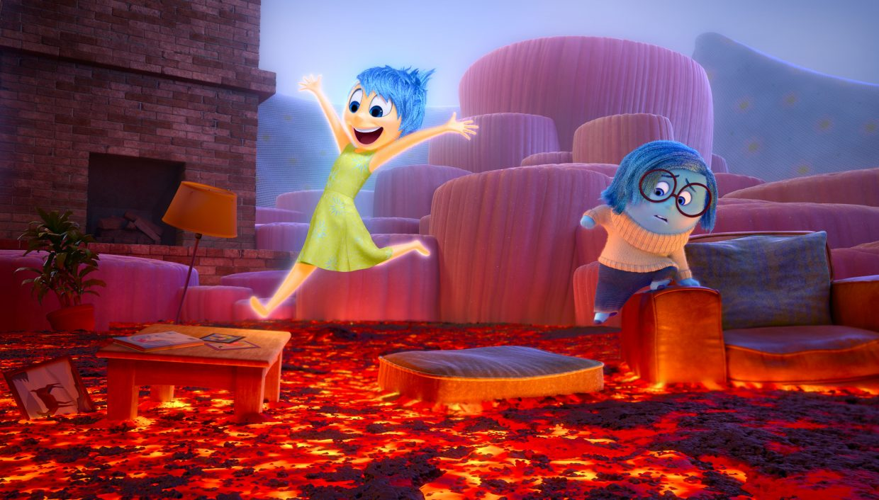 "Joy (Amy Poehler) and Sadness (Phyllis Smith) leap across a fantasy living room full of lava in ""Inside Out."" The movie is about an 11-year-old girl who struggles with living in a new city, partly because of a conflict between the voices in her head that guide her emotions."