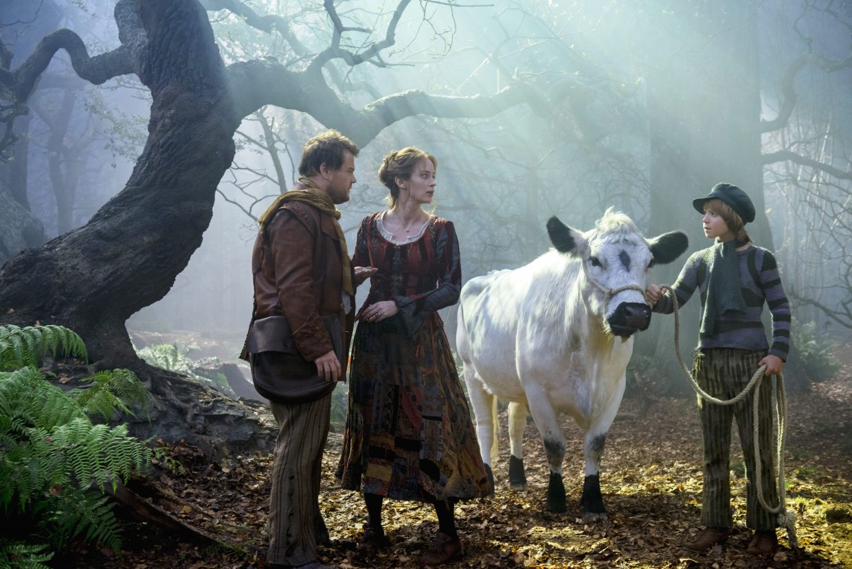 """The baker and his wife (James Corden, Emily Blunt) try to persuade the impressionable Jack (Daniel Huttlestone) to sell his cow, Milky White, in """"Into the Woods."""" The movie is a musical with multiple fairy tale characters pursuing their dreams."""