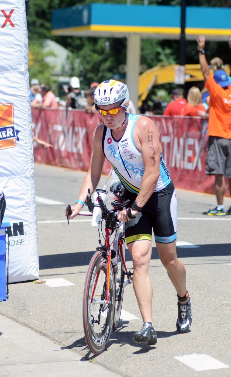Jim McCreight hops off his bike at the transition zone between the 112-mile cycling portion and the marathon Sunday at the Boulder Ironman.