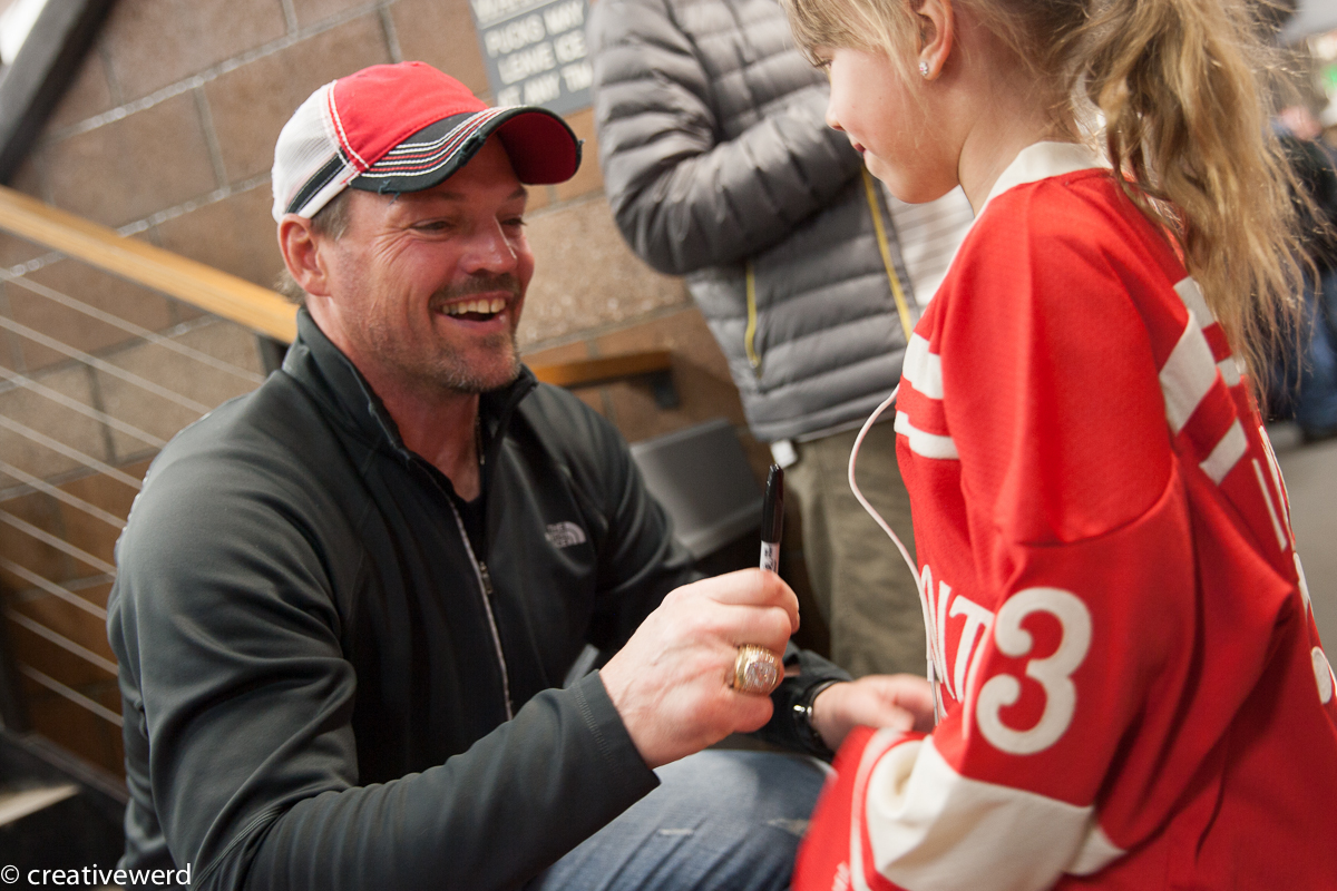 """Former Detroit Red Wing, Vancouver Canuck, New York Ranger and """"Bruise Brother"""" Joe Kocur signs an autograph for a young fan at last year's Alumni Classic."""