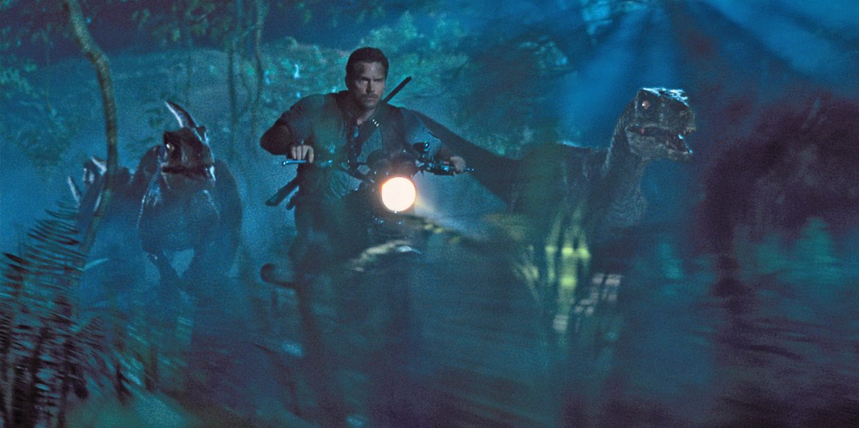 """Owen Grady (Chris Pratt) leads a pack of velociraptors through the jungle in """"Jurassic World."""" The movie is a reboot of the series about a theme park with living dinosaurs."""