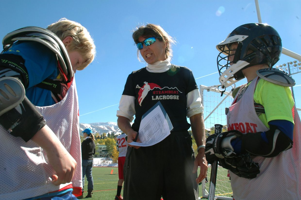 Steamboat Springs High School girls lacrosse coach Betsy Frick gives instructions to 11-year-old Ryan McNamara, left, and 10-year-old Daniel Kempers during the second annual Steamboat Chumash Challenge on Sunday morning at Gardner Field.