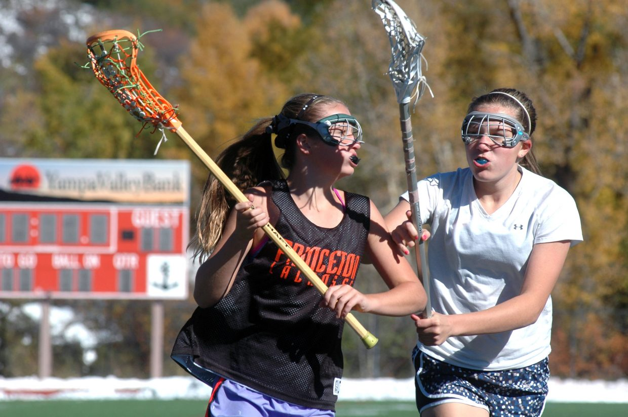 Eighth-grader Sage Quigley, left, of Boulder, tries to elude a check by Steamboat Springs High School freshman Maura Glynn on Sunday afternoon during the Steamboat Chumash Challenge.