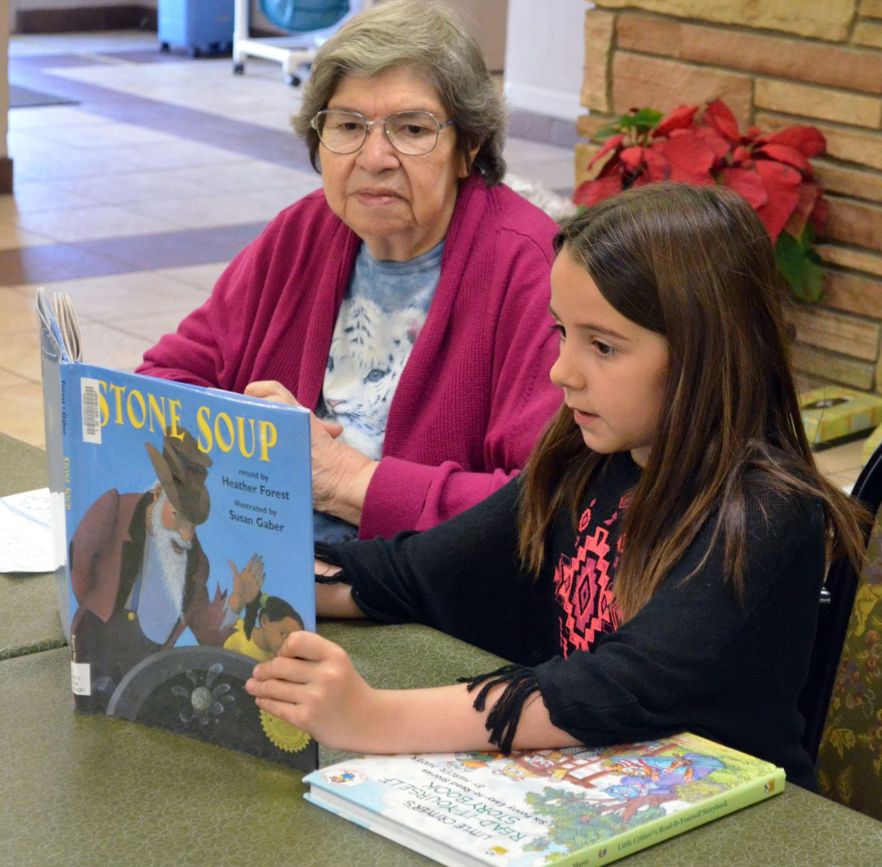Calvary Baptist School's Delilah Wilhelm reads from one of her favorite books to Mary Jo Brown, a resident of Sandrock Ridge Care & Rehabilitation. Students from the private school provided cheer to the people of Sandrock Ridge in mid-April.
