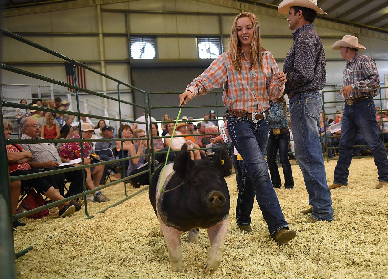 Jaycee May works her reserve grand champion hog around the pen Saturday at the Routt County Fair Junior Livestock sale in Hayden.