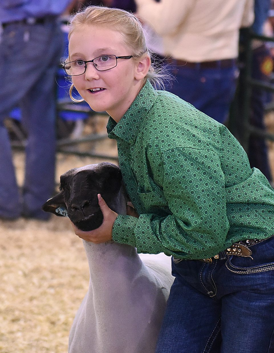 Larhae Whaley hangs tight while showing off her sheep Saturday at the Routt County Fair Junior Livestock sale in Hayden.