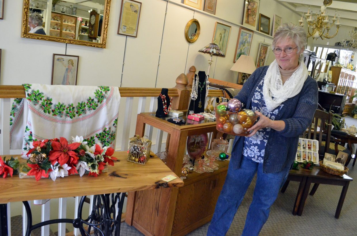 Yvonne Gerber holds up a bundle of Christmas ornaments among the sales items at Favorite Things, 584 Yampa Ave. Gerber has owned the downtown antique shop for about 14 years, a co-owner with Sherri Fredrickson. The store is full of vintage furniture, decorations, curios and more from years past.