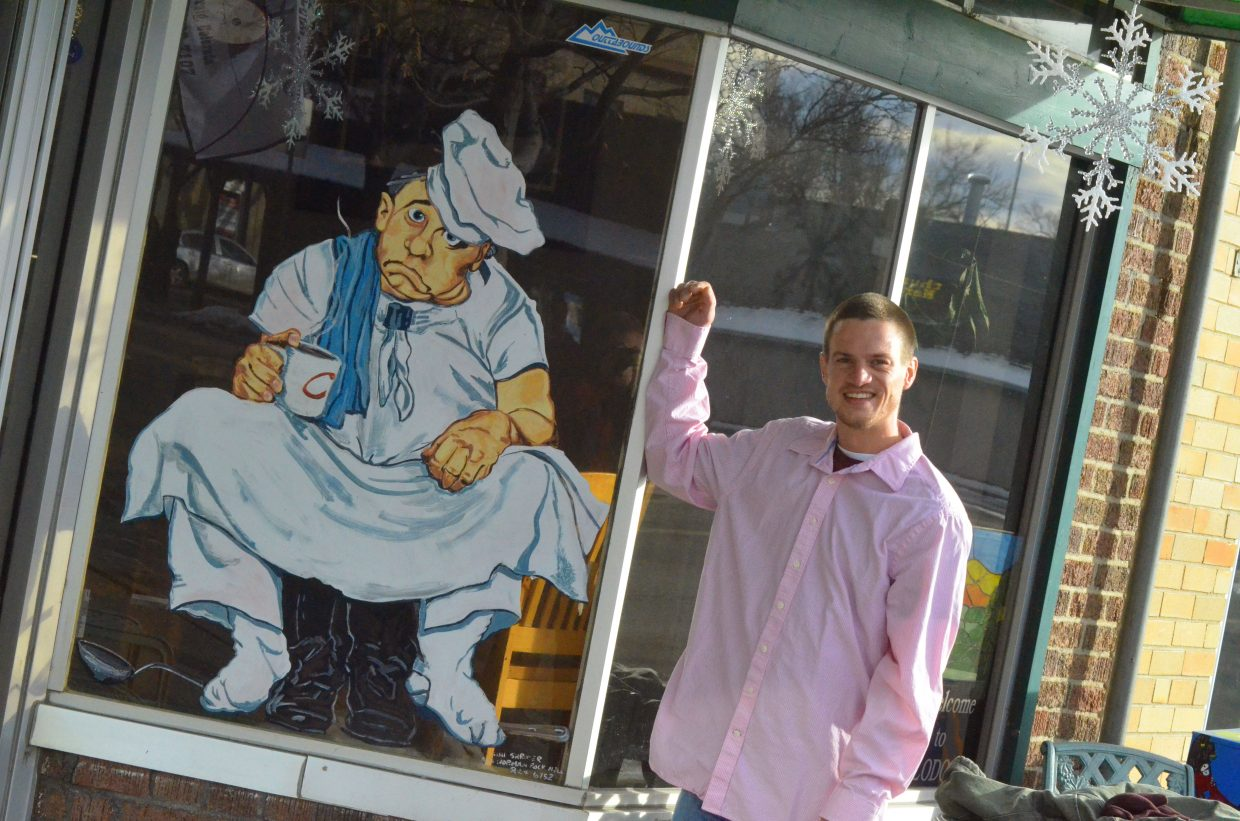 Adam Mercier leans against the front window of his workplace, Carell's Pizzeria & Pasta, a facade which includes a painting of a weary chef and seasonal snowflakes. Mercier handles unloading food trucks for the restaurant.