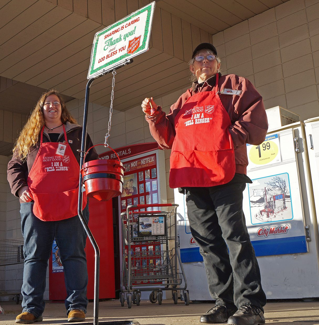 Volunteers April Vikse, left, and Tammy Boutwell ring bells and seek donations outside of City Market.