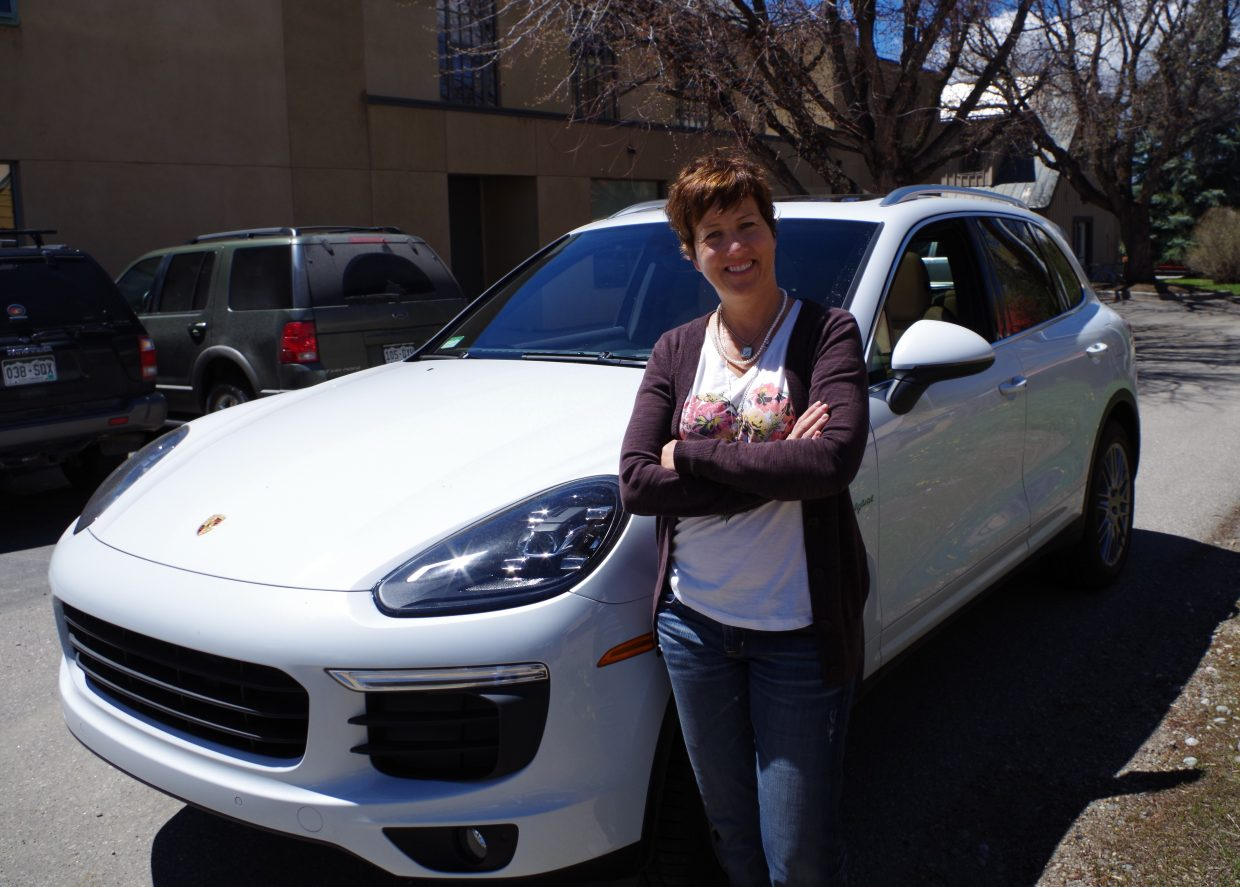 Luanne Feldmann stands next to her 2015 Porsche Cayenne SUV plug-in hybrid that gets the equivalent of 47 miles to the gallon.
