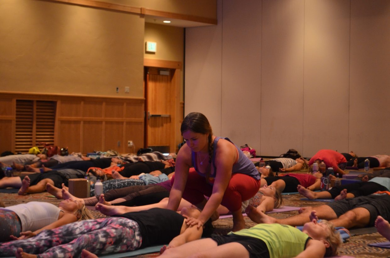 """In this photo one of Gina Capputo's assisting instructors aids one of the attendees in a pose throughout her """"Yogini on the loose"""" class at the Steamboat Movement Fest this weekend."""