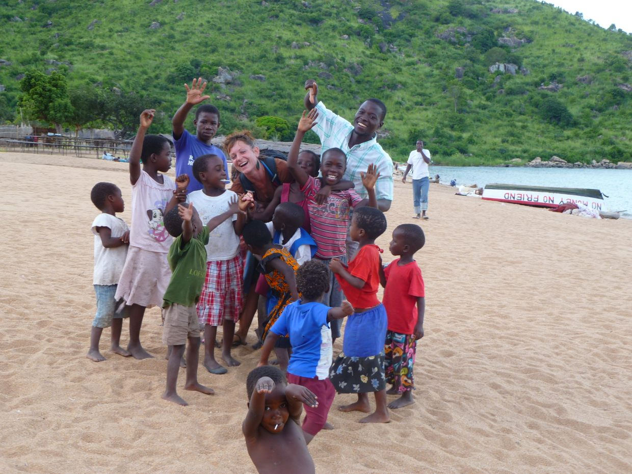 Grace Hampton is embraced by locals of Malawi, Africa.
