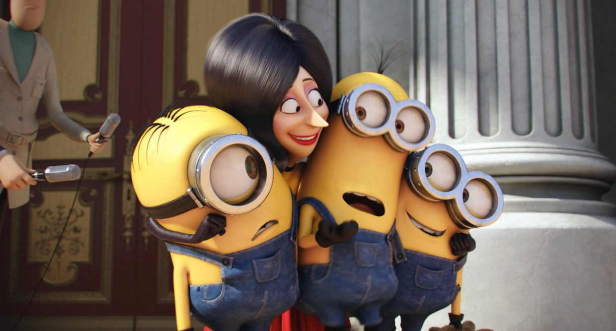 "Villain Scarlett Overkill (voice of Sandra Bullock) squeezes Minions Stuart, Kevin and Bob (Pierre Coffin) in ""Minions."" The movie is a spin-off and prequel to the ""Despicable Me"" films, showing how the small, yellow henchmen came to be."